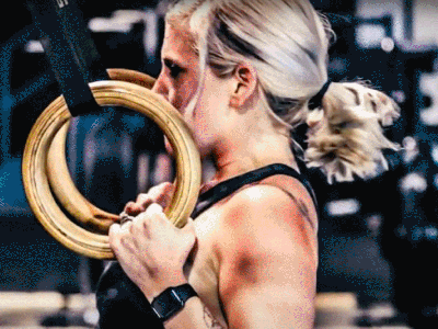 A woman training on the rings at boot camp.